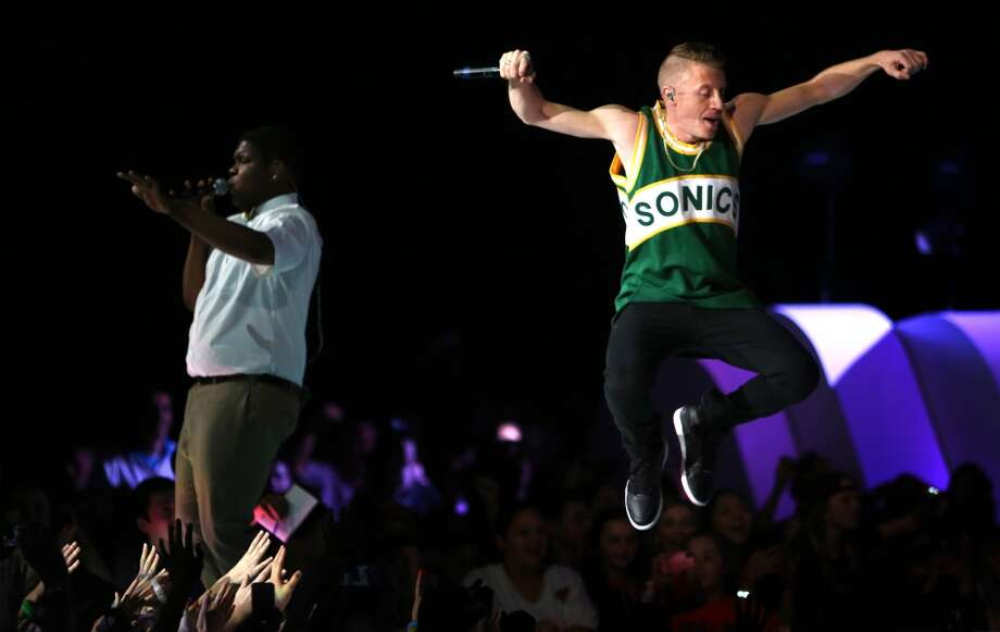 Macklemore and Ray Dalton, left, perform during We Day on Wednesday, March 27, 2013 at KeyArena in Seattle. The event brought thousands of middle and high school students together to hear from a list of celebrities and motivational speakers. We Day is a youth educational and empowerment event organized by the Free the Children charity. Students earn a seat at the event through their commitment to do good. (Joshua Trujillo, seattlepi.com) Photo: JOSHUA TRUJILLO