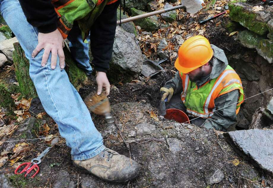New York State Museum archaeologists Aaron Gore, left, and Daniel Mazeau look for archaeological remains, in an excavation unit, dating as far back to approximately 8,000 B.C. at a dig site at Million Dollar Beach on Thursday, Oct. 31, 2013 in Lake George, N.Y. The New York State Museum's Cultural Resource Survey Program is currently conducting archaeological investigations in advance of a construction project.  (Lori Van Buren / Times Union) Photo: Lori Van Buren / 00024464A