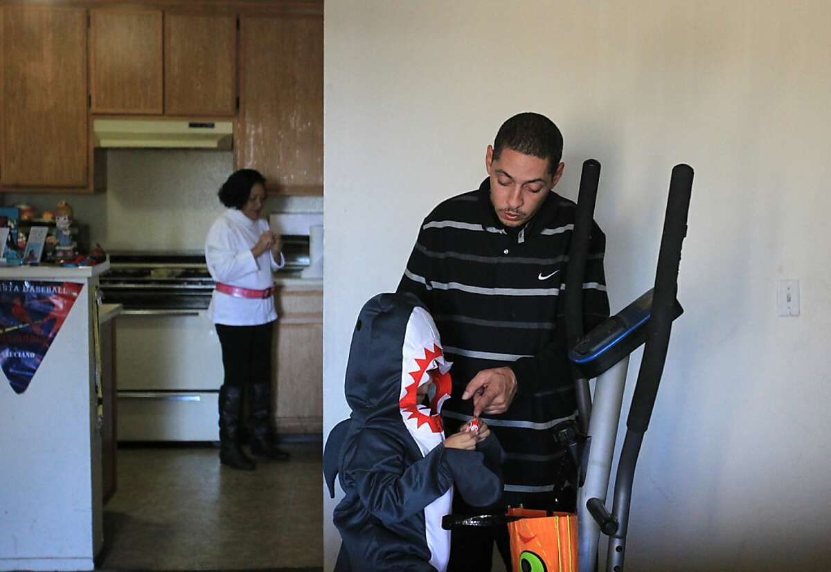 Miguel Alvarez, 33, helps his son Lucciano Alvarez, 4, unwrap a piece of candy as Alvarez's mother, Leida Alvarez, stands in the kitchen before an evening of trick-or-treating October 31, 2013 in Alvarez's home that he shares with his mother, wife, son and step son in San Leandro, Calif.