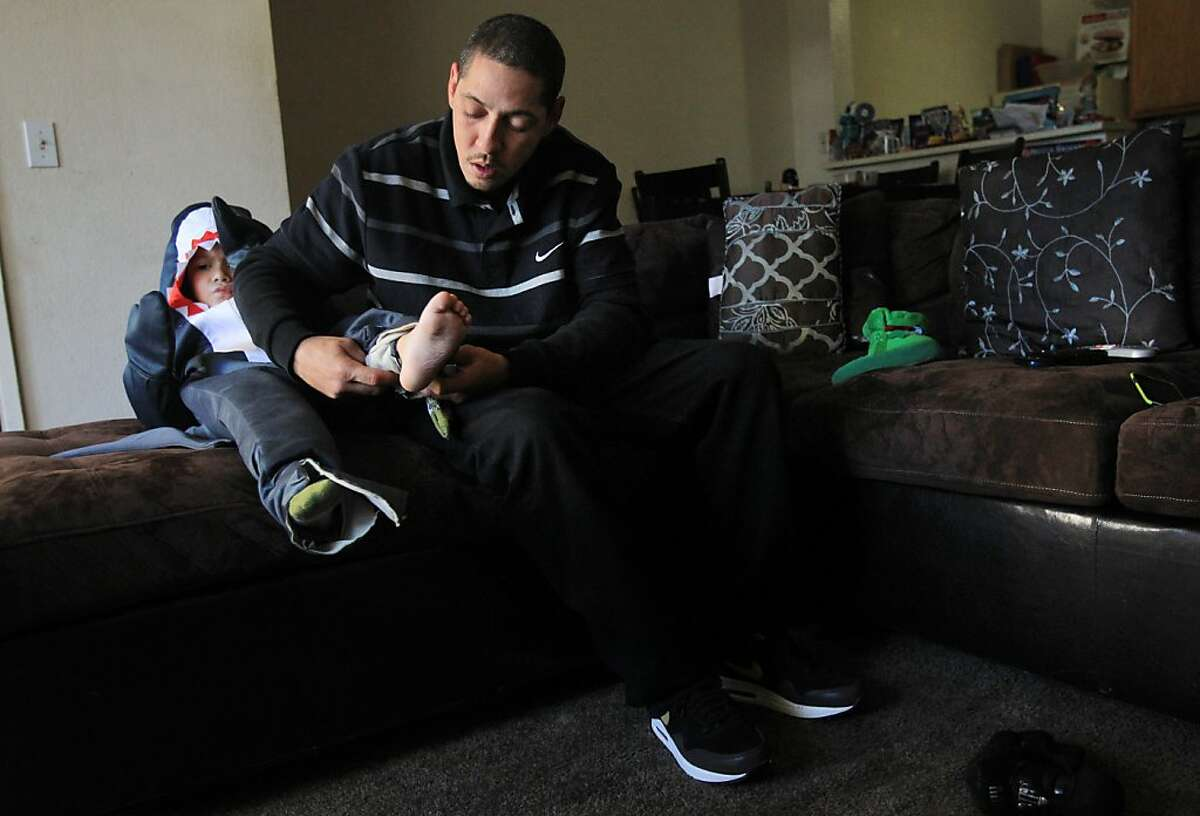 Miguel Alvarez helps son Lucciano, 4, get dressed in their San Leandro home in October. The Valley Springs Manor janitor took care of residents left alone.