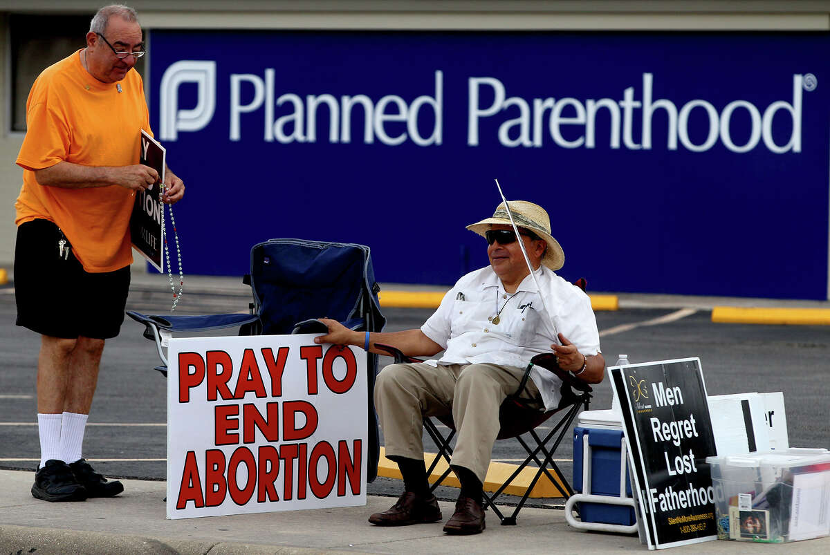 Phil Trickett (left) stands by Bob Cantu (right) with anti-abortion signs Tuesday October 26, 2013 in front of Planned Parenthood on Babcock Road. A federal Judge Monday struck down as unconstitutional a key provision of a Texas abortion law and partially blocked another regulation.