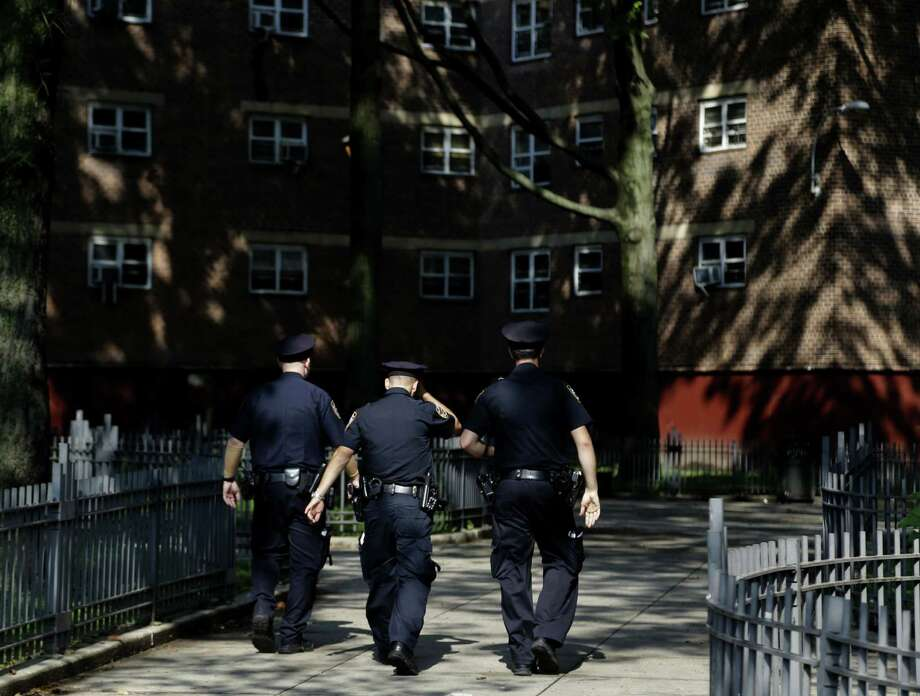 FILE - In this Aug. 13, 2013 file photo, police officers walk through the Brownsville Houses the Brownsville section of Brooklyn, New York. A federal appeals court on Thursday, Oct. 31, 2013, blocked a judge's order requiring changes to the New York Police Department's stop-and-frisk program and removed the judge from the case. (AP Photo/Seth Wenig, File) ORG XMIT: NYSW118 Photo: Seth Wenig / AP