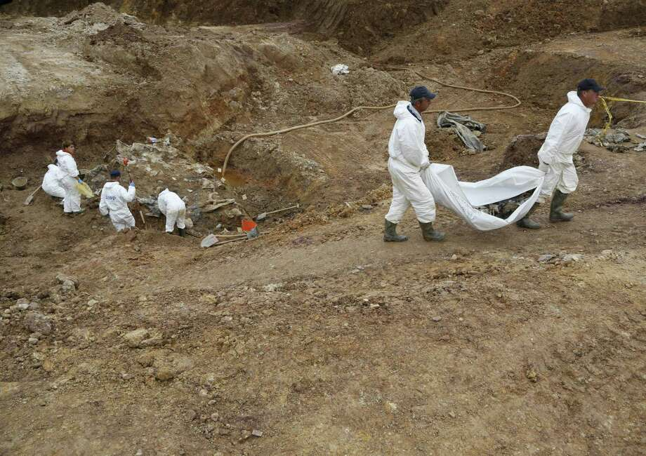 Forensic experts, members of the International Commission on Missing Persons, and Bosnian workers search for human remains Thursday at a mass grave in the village of Tomasica. Photo: Amel Emric / Associated Press