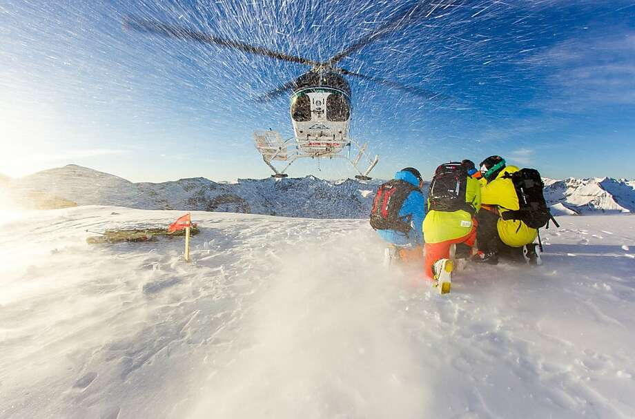 Skiers take shelter as the helicopter that dropped them off lifts up from the mountaintop. They have slopes of fresh, untracked powder to explore. Photo: Jeff Cricco, Helitrax