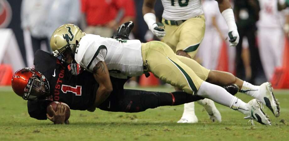 Cougars quarterback Greg Ward Jr. left, is tackled by South Florida Bulls safety Mark Joyce. Photo: James Nielsen, Houston Chronicle