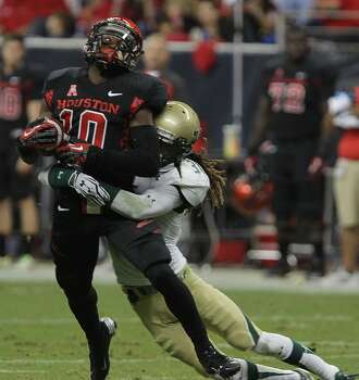 Cougars wide receiver Demarcus Ayers left, is tackled by South Florida Bulls defensive back Brandon Salinas. Photo: James Nielsen, Houston Chronicle