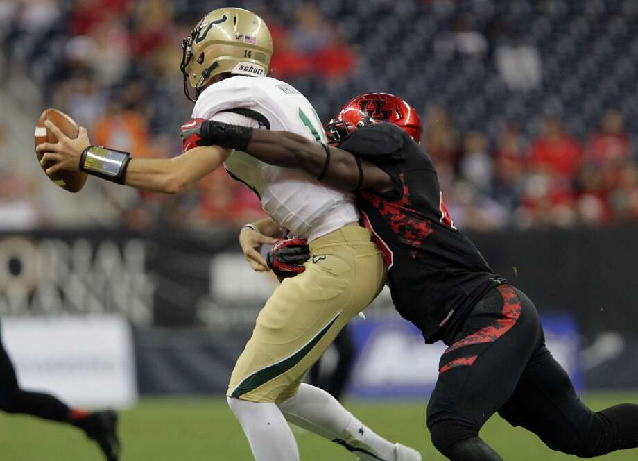 South Florida Bulls quarterback Mike White left, is tackled by Cougars linebacker Derrick Mathews. Photo: James Nielsen, Houston Chronicle