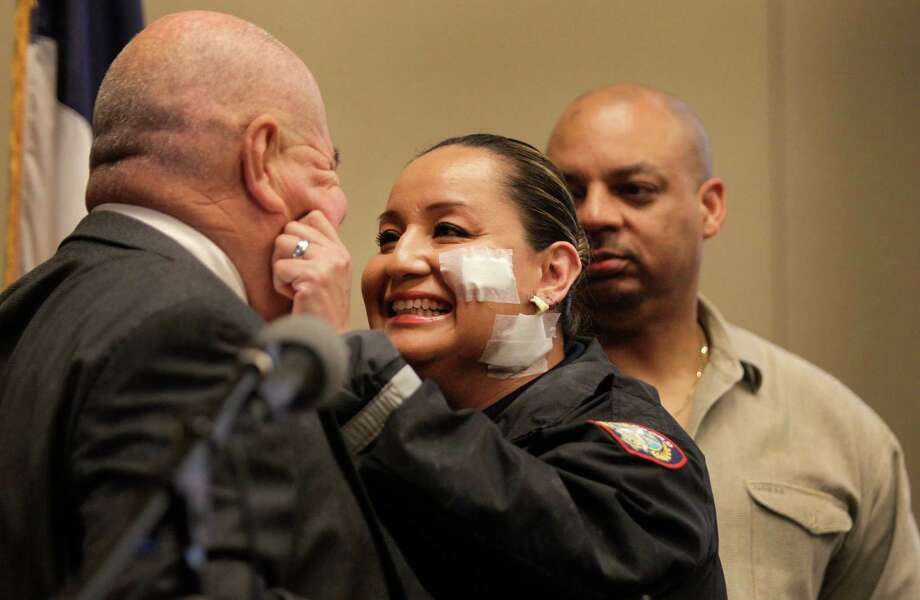 Stafford police officer Ann Carrizales pinches the cheeks of Police Chief B.R. Krahn at the Stafford Centre on Thursday.  She was wounded in a traffic stop Oct. 26. Her husband, Chris Mathis, is shown at right. Photo: Melissa Phillip, Staff / © 2013  Houston Chronicle