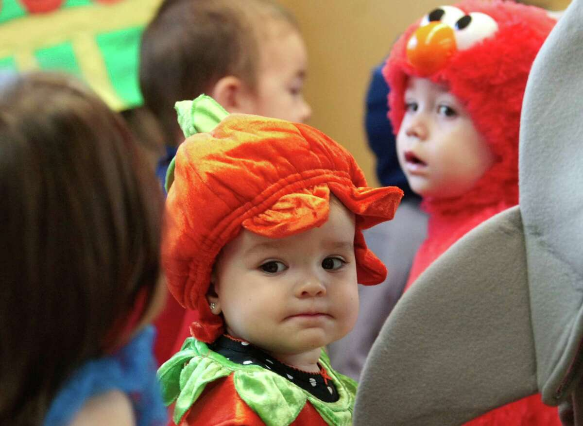 Lillian Niklas, dressed as a pumpkin, and Aidan Plowman, dressed as Elmo, walk in the parade of costumes Thursday October 31, 2013 at Primrose School of College Park in The Woodlands, Tx.