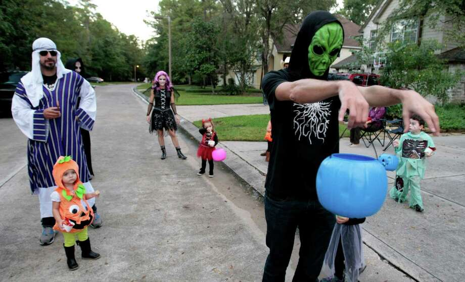 Pablo Medina, wearing a green alien mask, trick-or-treats with his family Halloween night. Photo: Billy Smith II, Chronicle / © 2013 Houston Chronicle