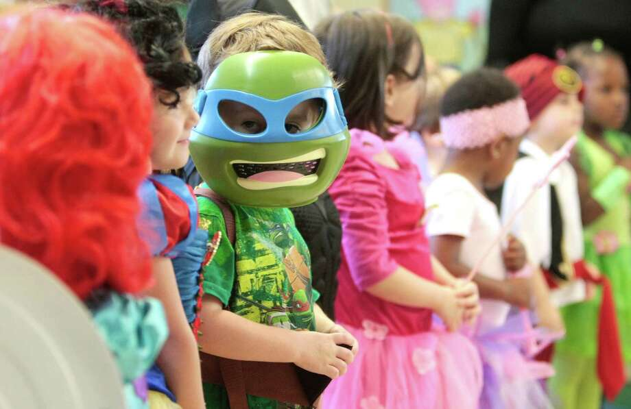 Three year-old Cameron Roye, dressed as a Teenage Mutant Ninja Turtle, sings with classmates Thursday October 31, 2013 during the Parade of Costumes. Photo: Billy Smith II, Chronicle / © 2013 Houston Chronicle