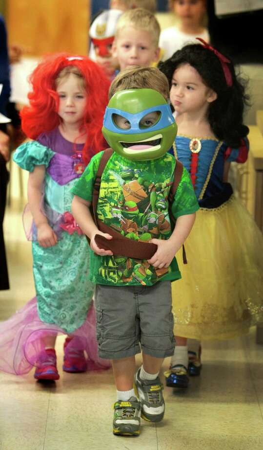 Three year-old Cameron Roye, dressed as a Teenage Mutant Ninja Turtle, leads his classmates Quinn McDonald, as the Little Mermaid, and three year-old Meagan Lacheny, as Snow White. Photo: Billy Smith II, Chronicle / © 2013 Houston Chronicle