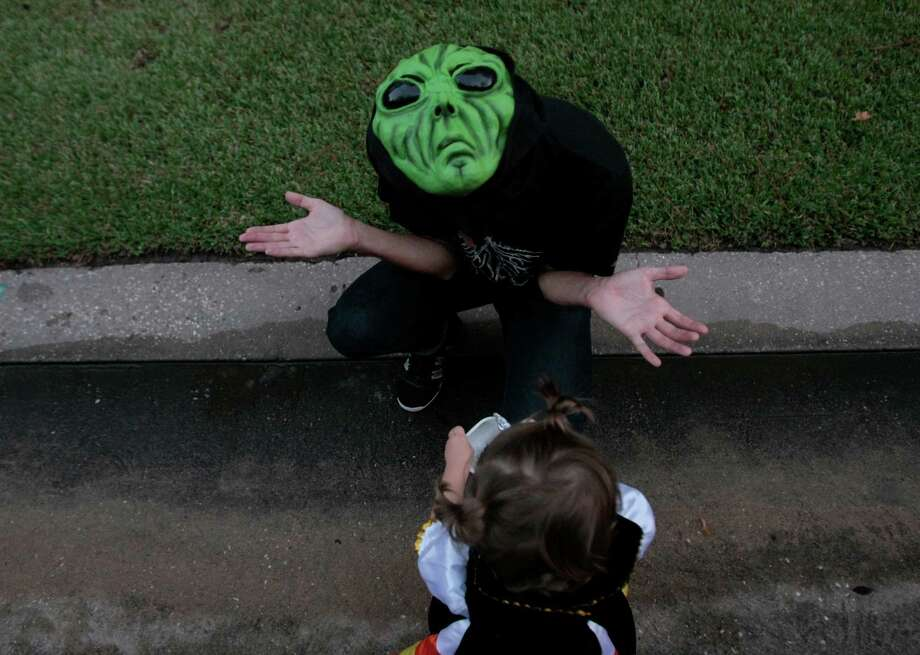 Pablo Medina, wearing a green alien mask, trick-or-treats with his daughter, one year-old Ines Medina, Halloween night in The Woodlands, Tx. Photo: Billy Smith II, Chronicle / © 2013 Houston Chronicle