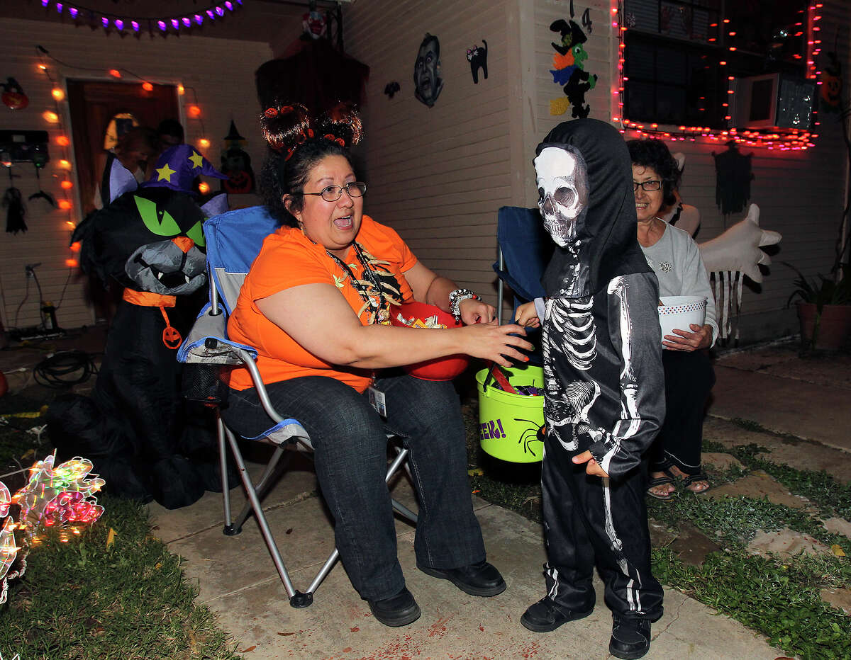Cindy Castillo is entertained by a skeleton as kids go trick-or-treating on the Southeast Side on October 31, 2013.