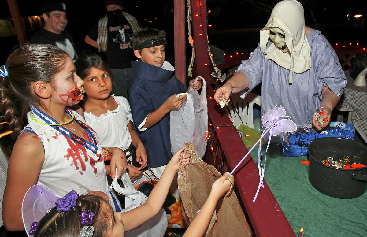 Corrine McGee hands out candy as kids go trick-or-treating on Hatcher Street on the Southeast Side on October 31, 2013.