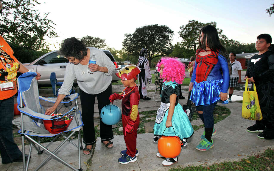 Maria Castillo hands out candy as kids go trick-or-treating on the Southeast Side  on October 31, 2013. Photo: TOM REEL
