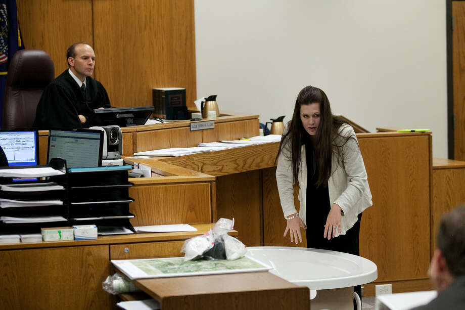 During testimony in Provo, Utah, Wednesday, Alexis Somers demonstrates the position in which her father, Martin MacNeill, told her he found his deceased wife. Photo: Mark Johnston / Associated Press
