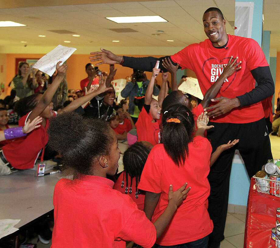 Dwight Howard congratulates students at Harmony School of Ingenuity on Thursday for winning the Rockets' second annual Food for Families competition. Photo: James Nielsen, Staff / © 2013  Houston Chronicle