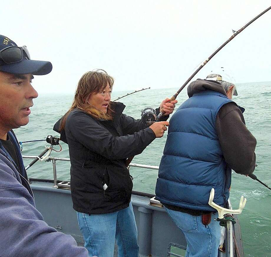 Jenna Tognoni (center) fights a salmon while deckhand John Dresser watches aboard the Wacky Jacky out of San Francisco. Photo: Brian Murphy, Handout