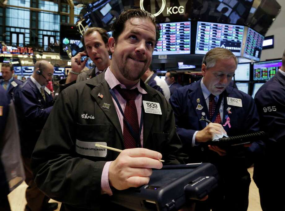 Trader Christopher Lotito, center, works on the floor of the New York Stock Exchange Thursday, Oct. 31, 2013. Stocks edged lower in early trading on Wall Street Thursday, paring the market's big gain for October. (AP Photo/Richard Drew) Photo: Richard Drew, STF / AP