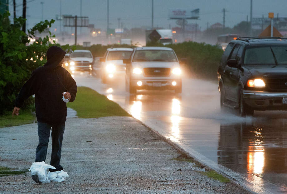 A man walking with bags on his feet to keep them dry watches as commuters drive through standing water near E Hamilton Street along the North Freeway access road, Thursday, Oct. 31, 2013, in Houston. Photo: Cody Duty, Houston Chronicle / © 2013 Houston Chronicle