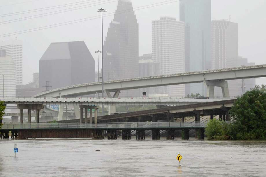 High water from White Oak Bayou is shown nearly covering the sidewalk signs along the bayou near Quitman and I-45 North Thursday, Oct.31, 2013. Although the area is designed for the overflow from the bayou, the water level is an impressive amount as it raises beyond its concrete barriers. Photo: Melissa Phillip, Houston Chronicle / © 2013  Houston Chronicle