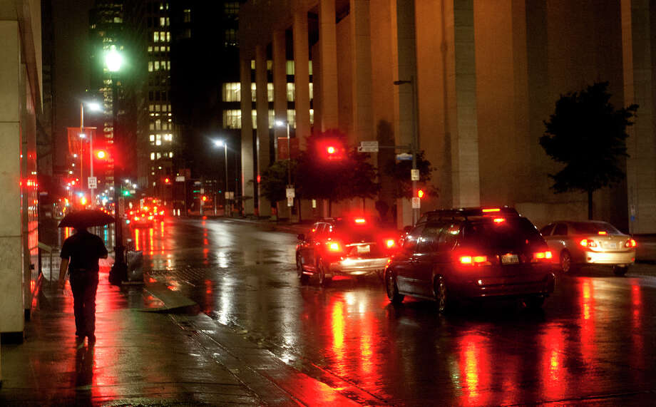 A pedestrian makes their way down Milam Street as rain reflects street lights and the car lights of early morning commuters Thursday, Oct. 31, 2013, in Houston. Photo: Cody Duty, Houston Chronicle / © 2013 Houston Chronicle
