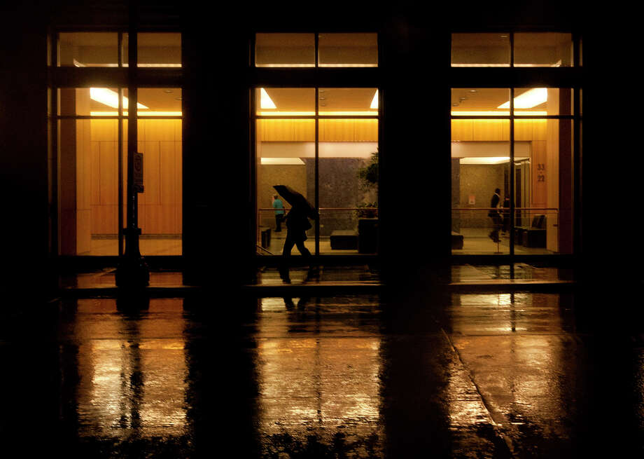 A pedestrian makes their way down Milam Street as rain reflects the light of a building Thursday, Oct. 31, 2013, in Houston. Photo: Cody Duty, Houston Chronicle / © 2013 Houston Chronicle