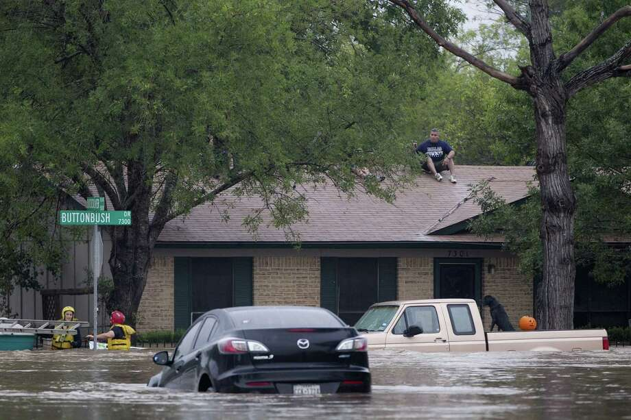 A man sits on top of a home on Buttonbush Drive in southeast Austin, Texas, on Thursday, October 31, 2013. Heavy overnight rains brought flooding to the area. Photo: Deborah Cannon, STATESMAN.COM / STATESMAN.COM