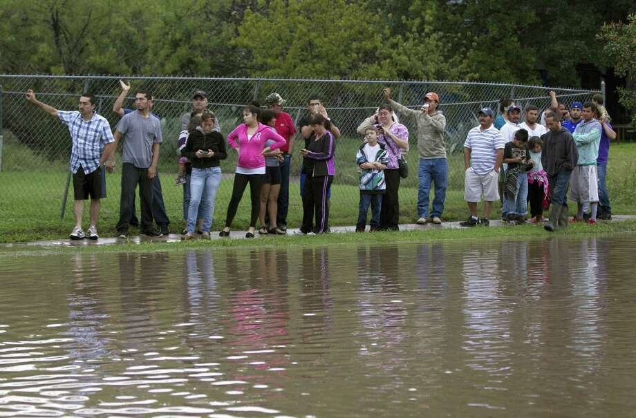People wait for flood waters to recede off Quicksilver Blvd in southeast Austin, Texas, on Thursday, October 31, 2013. Heavy overnight rains brought flooding to the area. Photo: Deborah Cannon, STATESMAN.COM / STATESMAN.COM