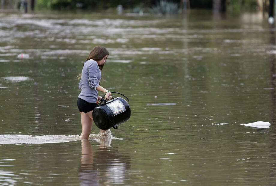 Alexis Wiesman, 14, helps to retrieve some belongings that were washed away from the floods from her grandparents home on Bluff Springs Road in Austin, Texas, Thursday, October 31, 2013. Overnight and early morning rains once again saturated the Austin area and caused major flooding along local creeks and low-lying areas. Photo: Ralph Barrera, STATESMAN.COM / STATESMAN.COM