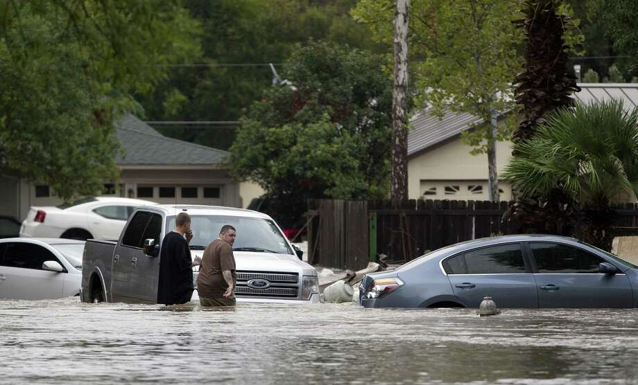 People walk near partially submerged cars on Canella Drive in southeast Austin, Texas, on Thursday, October 31, 2013. Heavy overnight rains brought flooding to the area. Photo: Deborah Cannon, STATESMAN.COM / STATESMAN.COM