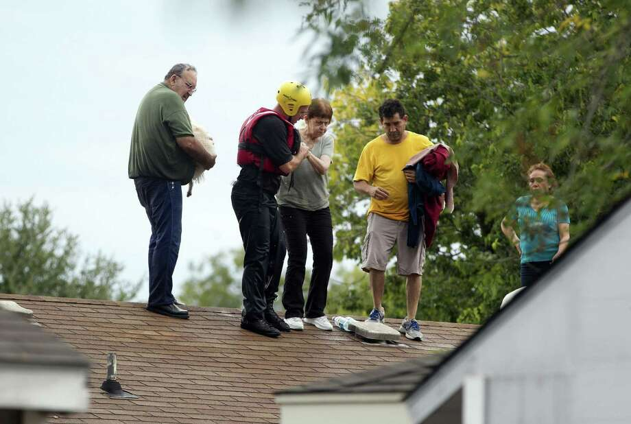 People are rescued from a home's rooftop on Canella Drive in southeast Austin, Texas, on Thursday, October 31, 2013. Heavy overnight rains brought flooding to the area. Photo: Deborah Cannon, STATESMAN.COM / STATESMAN.COM