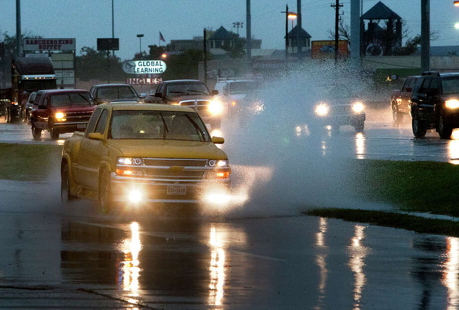 A commuter drives through standing water near E Hamilton Street along the North Freeway access road, Thursday, Oct. 31, 2013, in Houston. Photo: Cody Duty, Houston Chronicle / © 2013 Houston Chronicle