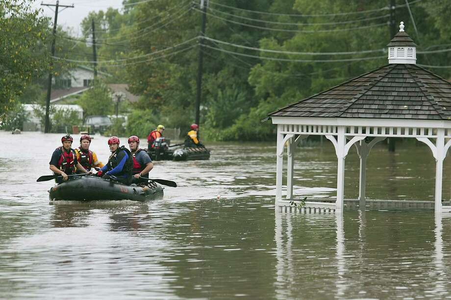Austin fire rescuers go through a neighborhood in search of anyone in need passing a gazebo that had floated into Bluff Springs Road in Austin, Texas, Thursday, October 31, 2013. Overnight and early morning rains once again saturated the Austin area and caused major flooding along local creeks and low-lying areas. Photo: Ralph Barrera, STATESMAN.COM / STATESMAN.COM