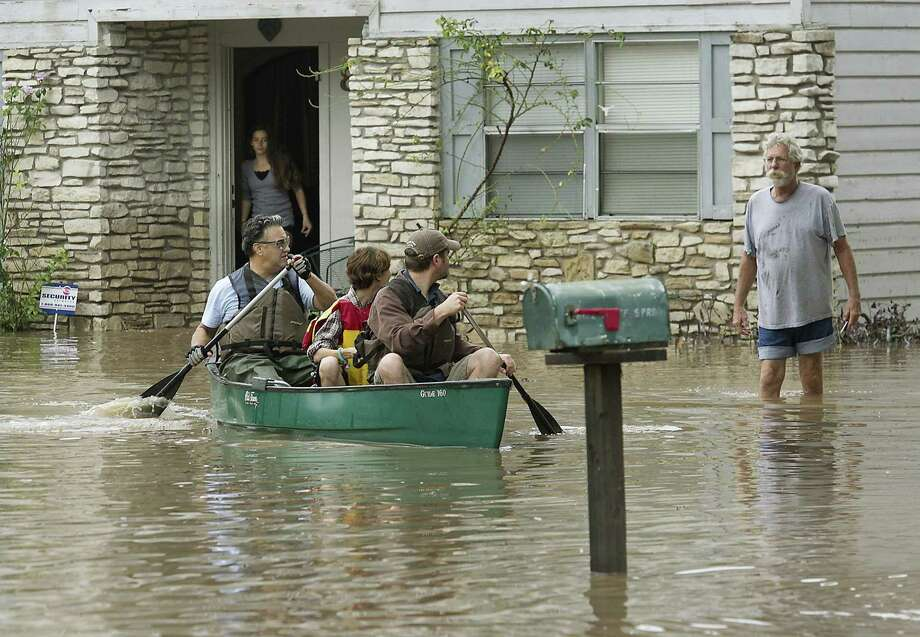 People paddle through flooded streets in search of anyone in need, like homeowner Jack Anderson and his grand daughter Alexis Wiesman, 14. Overnight and early morning rains once again saturated the Austin area and caused major flooding along local creeks and low-lying areas Thursday, October 31, 2013. Photo: Ralph Barrera, STATESMAN.COM / STATESMAN.COM