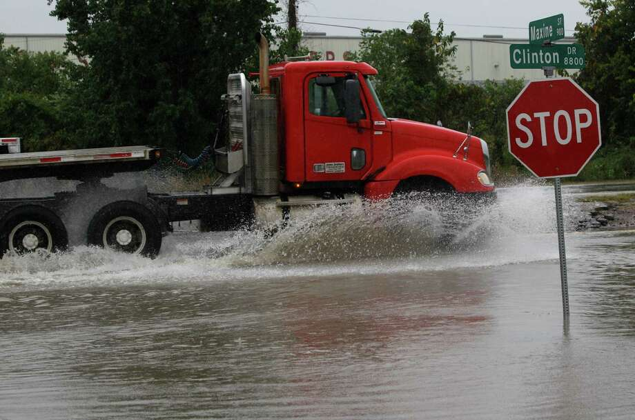 A tractor-trailer moves through high water along the 8800 block of Clinton near I-610 Thursday, Oct. 31, 2013, in Houston. Photo: Melissa Phillip, Houston Chronicle / © 2013  Houston Chronicle
