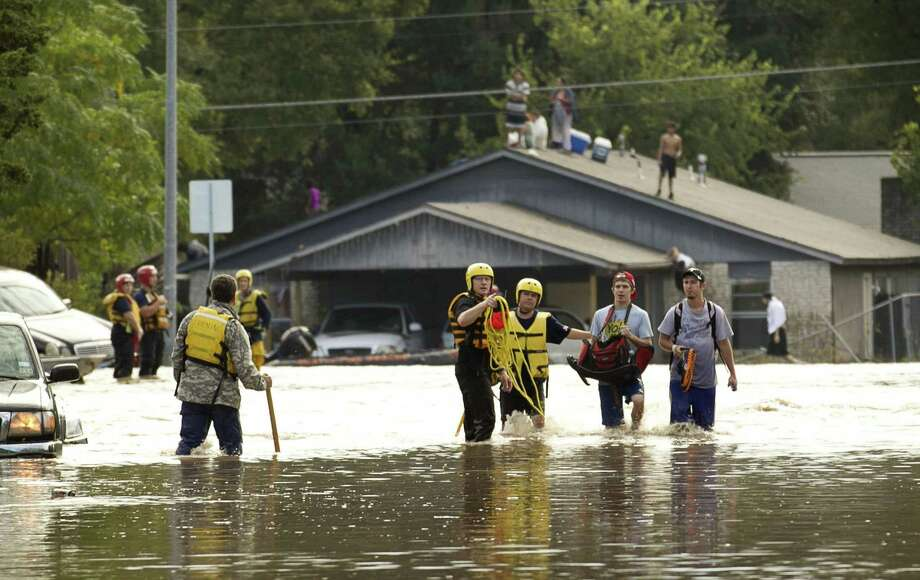 Tyler Pinnell, second from right, and his roommate Taylor McIntyre, wlak through the floodwaters on Quicksilver Boulevard in Austin, Texas, after leaving their flooded home on Canella Drive on Thursday, October 31, 2013. Photo: Jay Janner, STATESMAN.COM / STATESMAN.COM