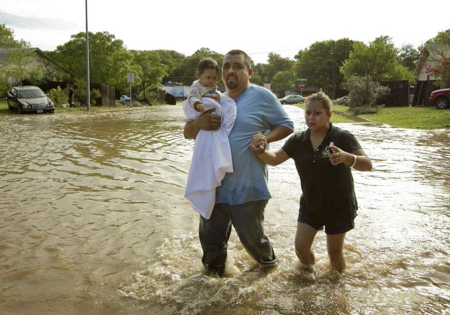 Israel Rodrigez, carries his 8-month-old daughter, Rubi, as he and his wife, Isabel, walk through flood waters, after their home in Austin, Texas, was flooded on Thursday, October 31, 2013. Photo: Jay Janner, STATESMAN.COM / STATESMAN.COM