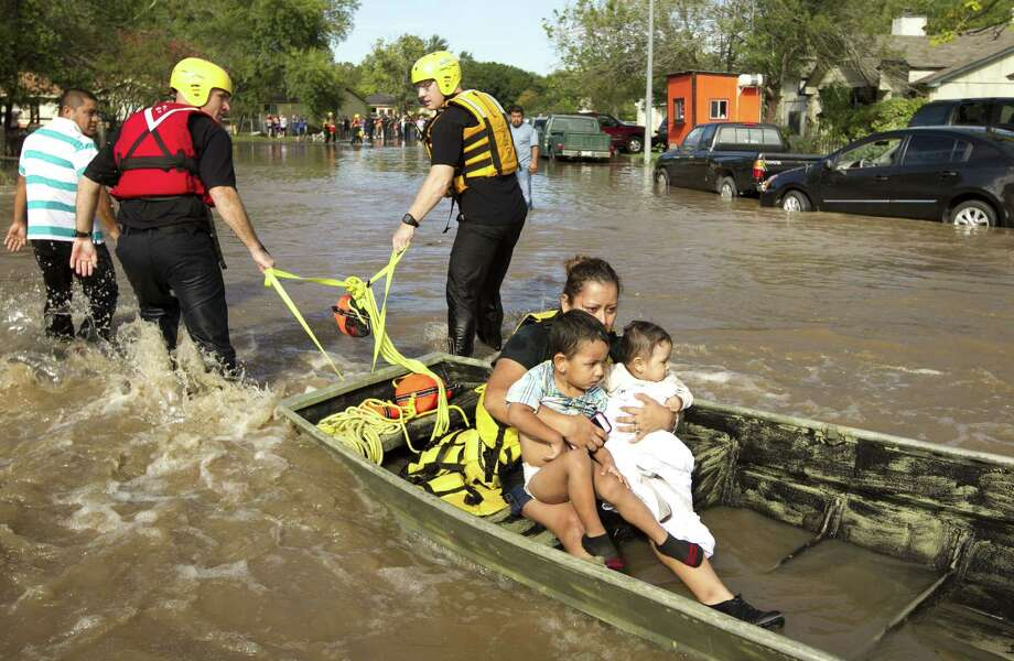 Isabel Rodriguez and her children Christopher, left, 3, and Rubi, 8 months, are carried on a boat on Quicksilver Boulevard in Austin, Texas, after their home on South Pleasant Valley Road was flooded on Thursday October 31, 2013. Photo: Jay Janner, STATESMAN.COM / STATESMAN.COM