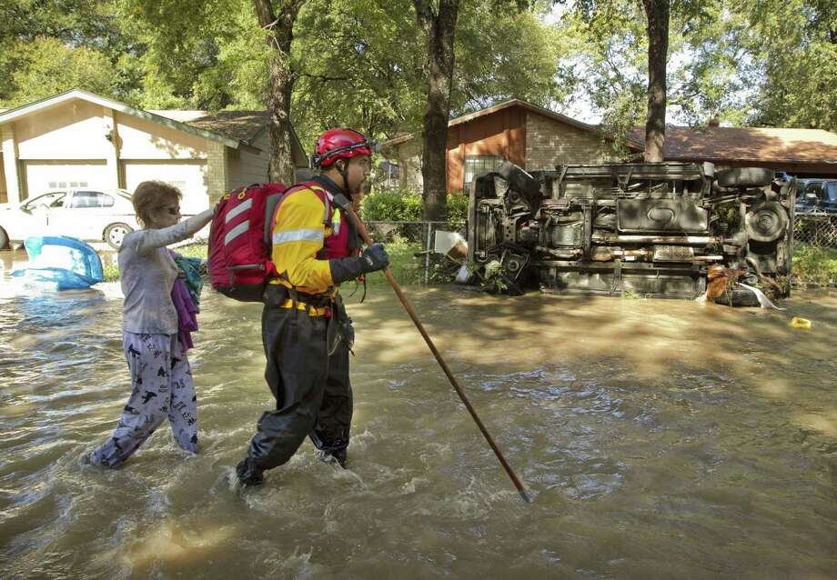 A rescuer leads a flood victim away from her flooded home on Wild Onion Drive in Austin, Texas, on Thursday, October 31, 2013. Photo: Jay Janner, STATESMAN.COM / STATESMAN.COM