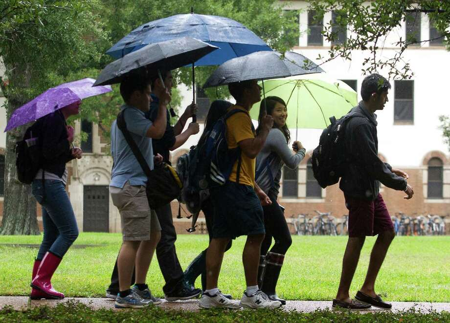 Rice University students walk to class during a wet morning on Thursday, Oct. 31, 2013, in Houston. Photo: J. Patric Schneider, For The Chronicle / © 2013 Houston Chronicle