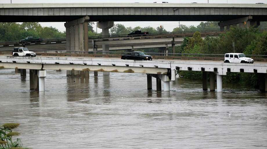 Cars travel along the exit ramp of I-45 onto I-10 over White Oak Bayou, which overflowed it's banks after a heavy downpour, Thursday, Oct. 31, 2013, in Houston. Photo: Karen Warren, Houston Chronicle / © 2013 Houston Chronicle