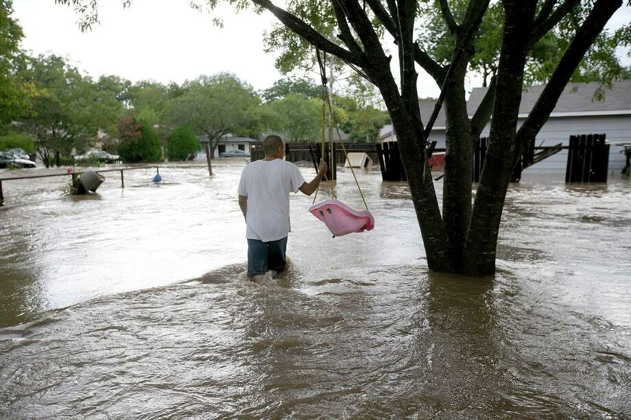 Alejandro Salazar holds on to a swing as he watches the flood waters move on Canella Drive in southeast Austin, Texas, on Thursday, Oct. 31, 2013. Heavy overnight rains brought flooding to the area. The National Weather Service said more than a foot of rain fell in Central Texas, including up to 14 inches in Wimberley, since rainstorms began Wednesday. Photo: Deborah Cannon, STATESMAN.COM / STATESMAN.COM