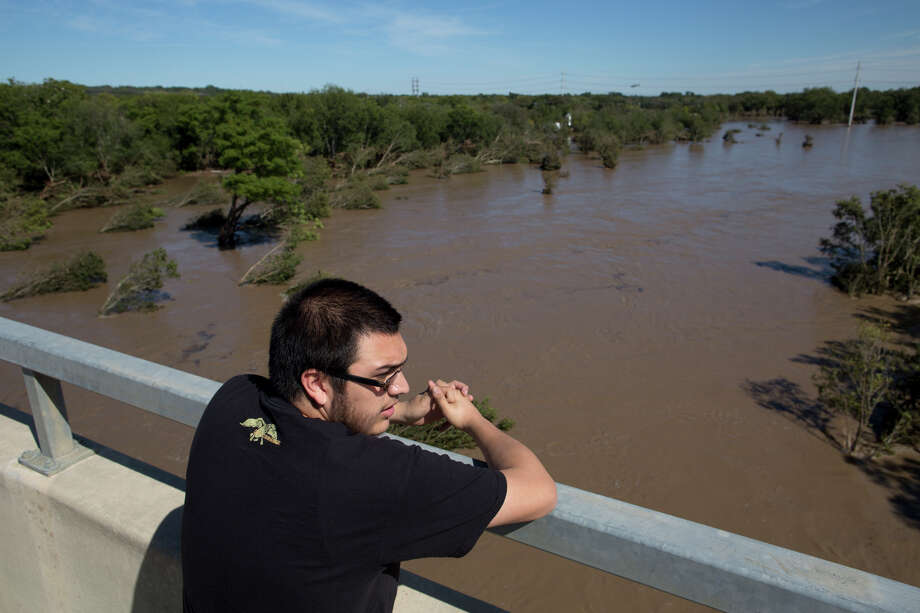 Jake Navarro looks out over a flooded Onion Creek on Thursday Oct. 31, 2013 in Austin, Texas.  The National Weather Service said more than a foot of rain fell in Central Texas, including up to 14 inches in Wimberley, since rainstorms began Wednesday. Photo: Tamir Kalifa, Associated Press / FR170773 AP
