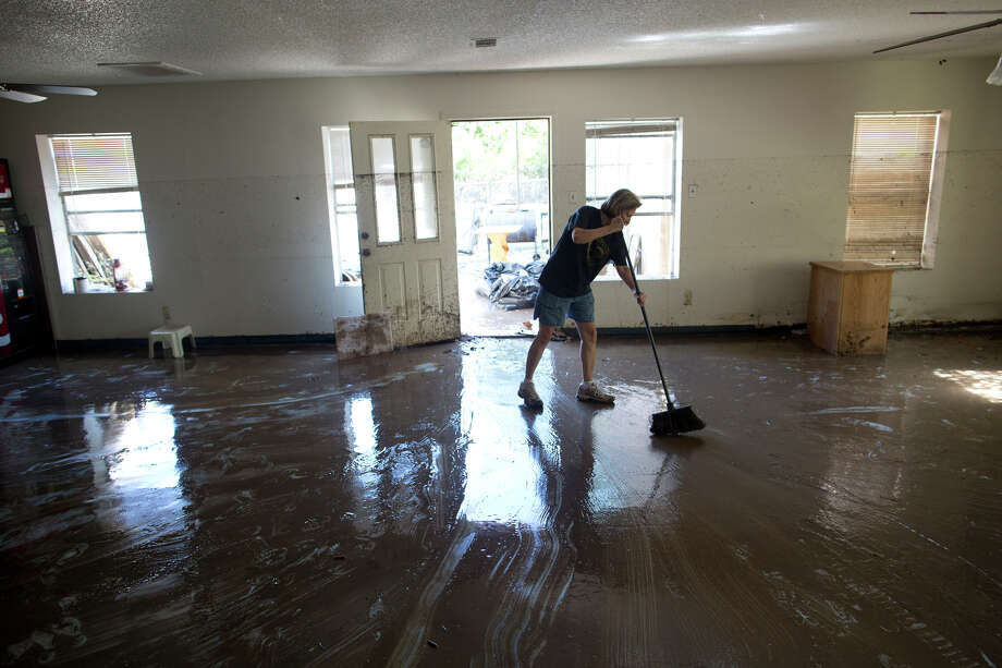 Diana Ward helps clean up the First Independent Baptist Church after heavy rains caused water levels to rise over four feet in the church before receding on Thursday Oct. 31, 2013 in Austin, Texas. The National Weather Service said more than a foot of rain fell in Central Texas. Photo: Tamir Kalifa, Associated Press / FR170773 AP