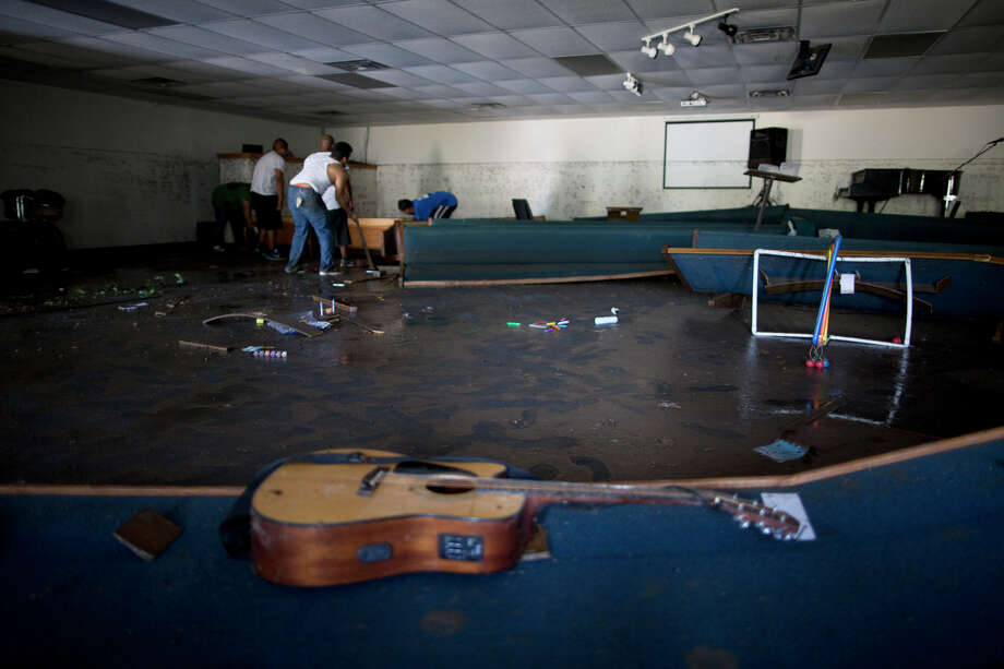Volunteers clean up the First Independent Baptist Church after heavy rains caused water levels to rise over four feet in the church before receding on Thursday Oct. 31, 2013 in Austin, Texas. The National Weather Service said more than a foot of rain fell in Central Texas. Photo: Tamir Kalifa, Associated Press / FR170773 AP
