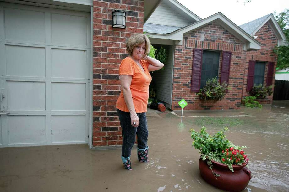 Barbara Smitherman stands in front of her flooded home in southeast Austin, Texas, on Thursday, Oct. 31, 2013. Heavy overnight rains brought flooding to the area. The National Weather Service said more than a foot of rain fell in Central Texas, including up to 14 inches in Wimberley, since rainstorms began Wednesday. Photo: Deborah Cannon, STATESMAN.COM / STATESMAN.COM