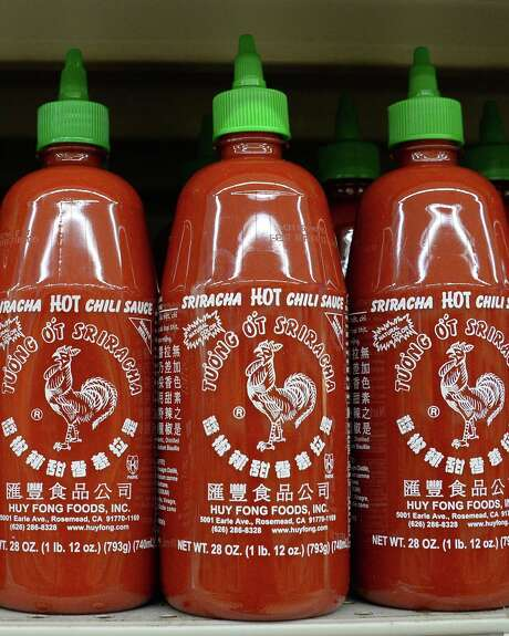 Bottles of Huy Fong brand Sriracha chili sauce are seen for sale at a grocery store in Los Angeles, California, October 30, 2013.   A row over spicy smells wafting from the Huy Fong factory is threatening to halt production of the popular chili sauce, as a judge mulls a legal challenge.  The California city of Irwindale, outside Los Angeles, has taken legal action against Sriracha maker Huy Fong Food's facility, after neighbors complained about strong odors.  AFP PHOTO / ROBYN BECKROBYN BECK/AFP/Getty Images Photo: ROBYN BECK, Staff / AFP