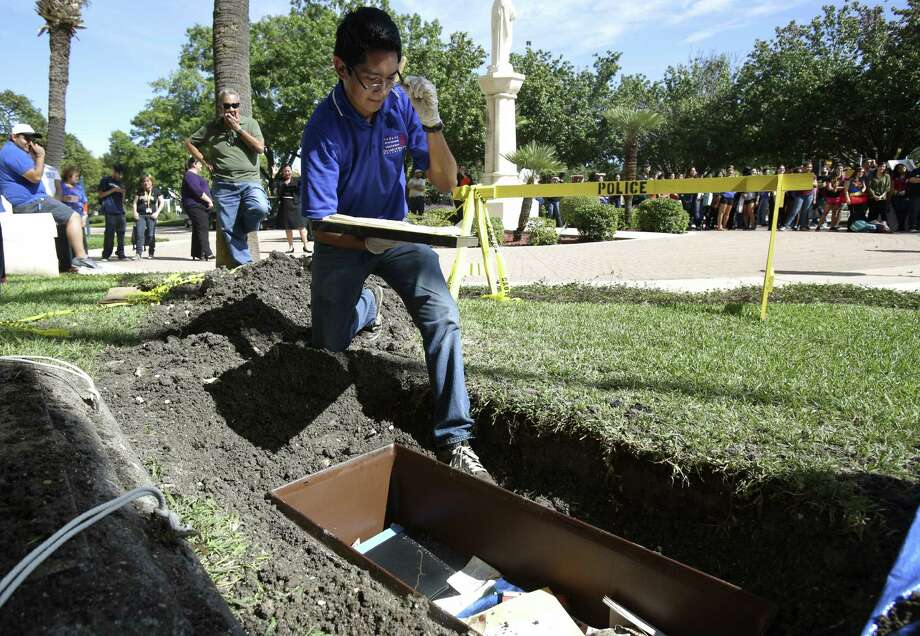 Cesar Rodriguez removes items from a time capsule at Our Lady of the Lake University. On Oct. 31, 1986, the university community placed items in the capsule and buried it in front of Main Building to celebrate the university's 75th anniversary. Photo: Helen L. Montoya / San Antonio Express-News